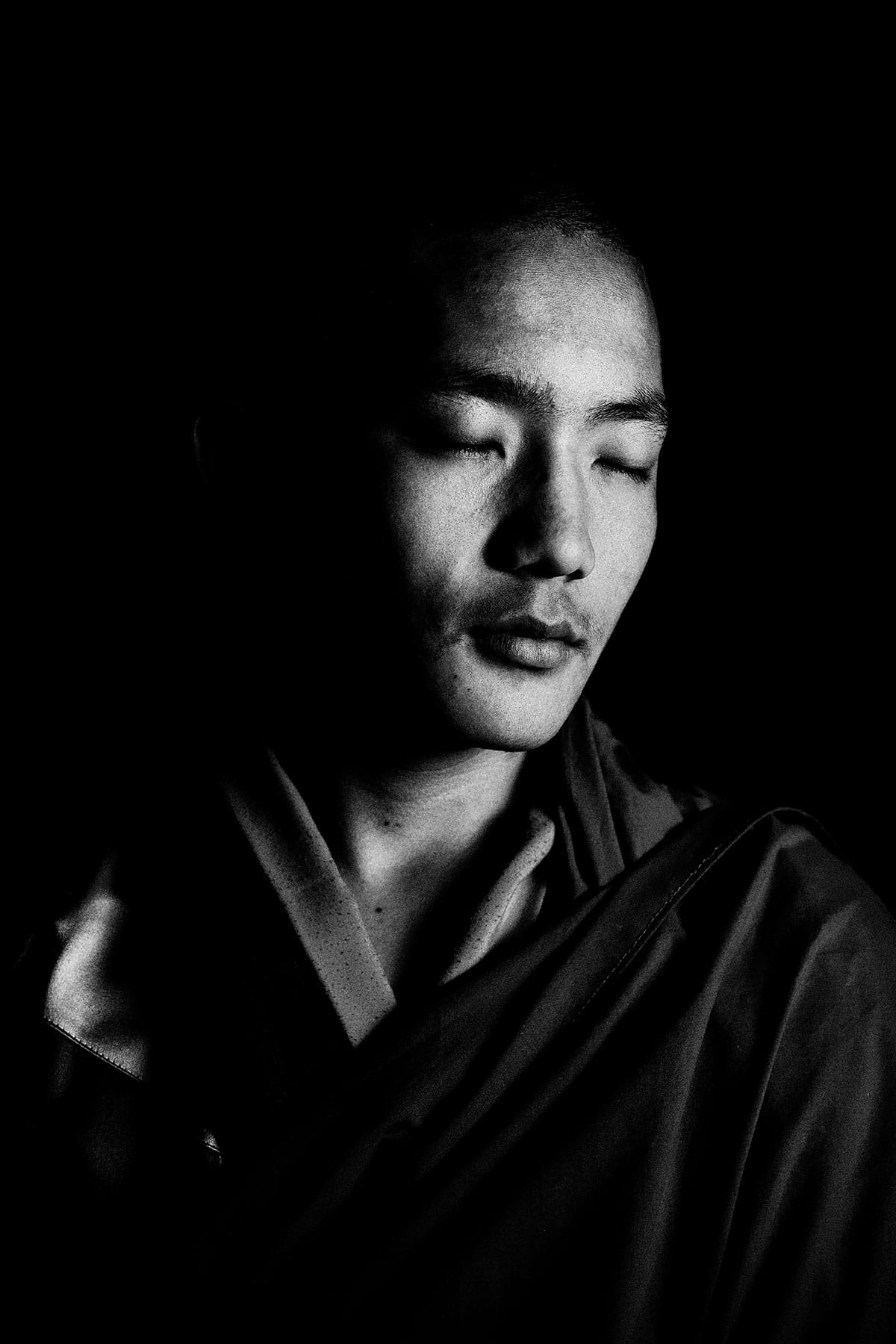 Eyes Closed Portrait of a Bhutanese Monk: Black and White Portrait Photography by Jean Tran and Élysée Lang