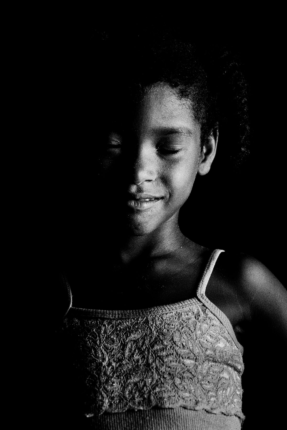 Eyes Closed Portrait of a Child from Ilha dos Lençóis: Black and White Portrait Photography by Jean Tran and Élysée Lang